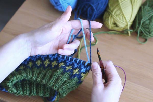 Dłonie trzymające robótkę nadrutach - układanie dwóch nitek wdłoni.