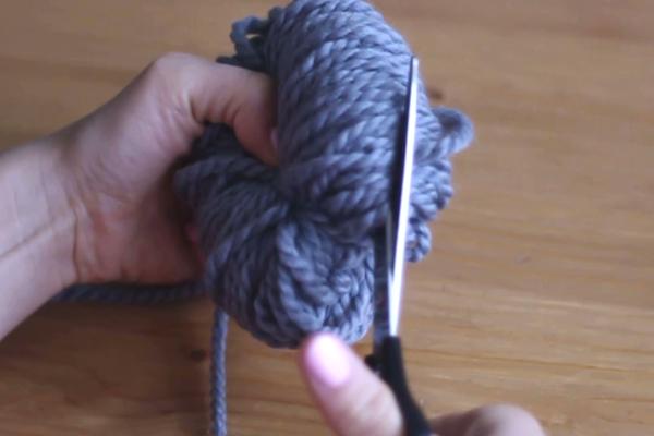 Rozcinanie pętelek szarej włóczki, takżebypowstał pompon.