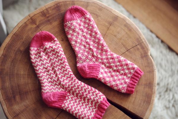 Różowo-żółte skarpetki zwzorem żakardowym ręcznie zrobione nadrutach, rozłożone napłasko.