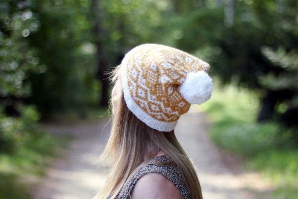 Dziewczyna wbiało-żółtej czapce zwzorem żakardowym ipomponem - czapka Goldenrod Hat