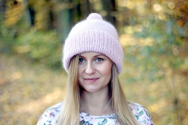 Dziewczyna zdługimi blond włosami wróżowej czapce zpomponem zrobionej ręcznie nadrutach. Wtle rozmazane liście.