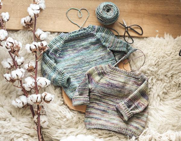 Dwa dziecięce sweterki robione nadrutach, jeden ma niedokończony rękaw. Rozłożone napłasko. Obok leżą kłębek włóczki, nożyczki ikwiaty bawełny.