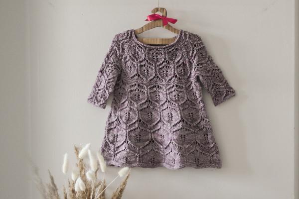 Sukieneczka niemowlęca zrobiona nadrutach zwzorem ażurowym, powieszona nawieszaku naścianie.