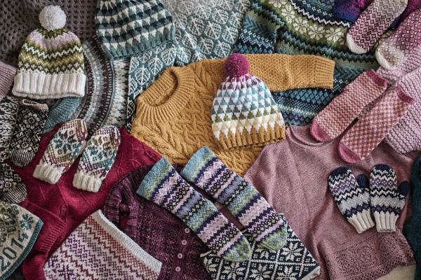 Rozłożone naziemi swetry, czapki, skarpety, rękawiczki zkolorowymi wzorami żakardowymi, zrobione nadrutach.